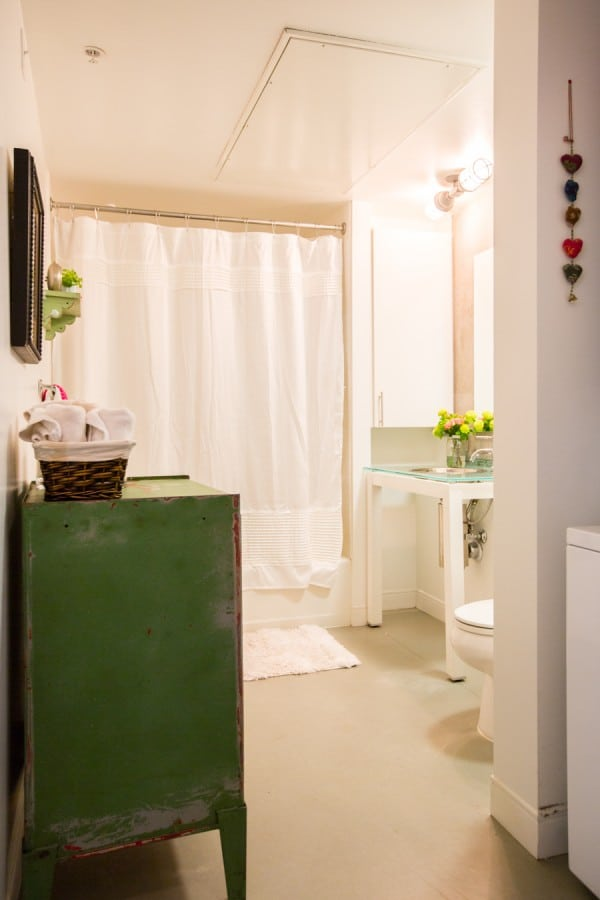 Pretty white bathroom with green cabinet