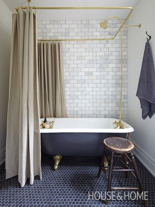 Gray and White Clawfoot Tub with Subway Tile and Brass Fittings