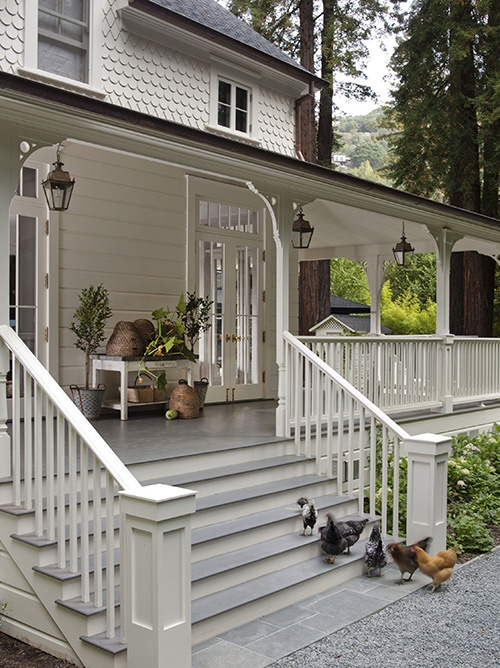 White Farmhouse - Wraparound Porch with Hanging Lanterns