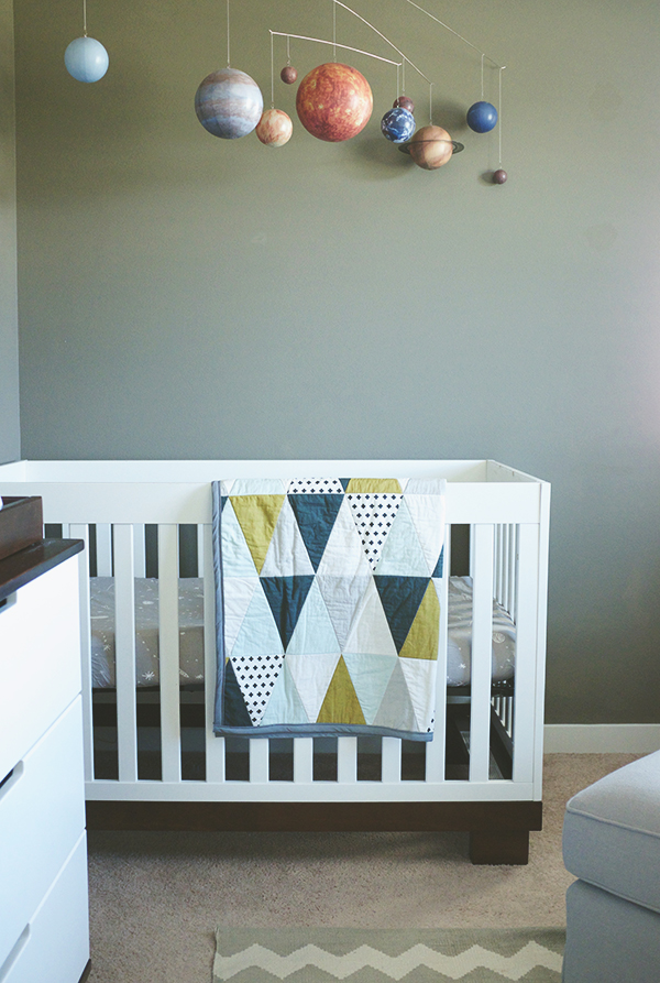 nursery with planet mobile and triangle quilt