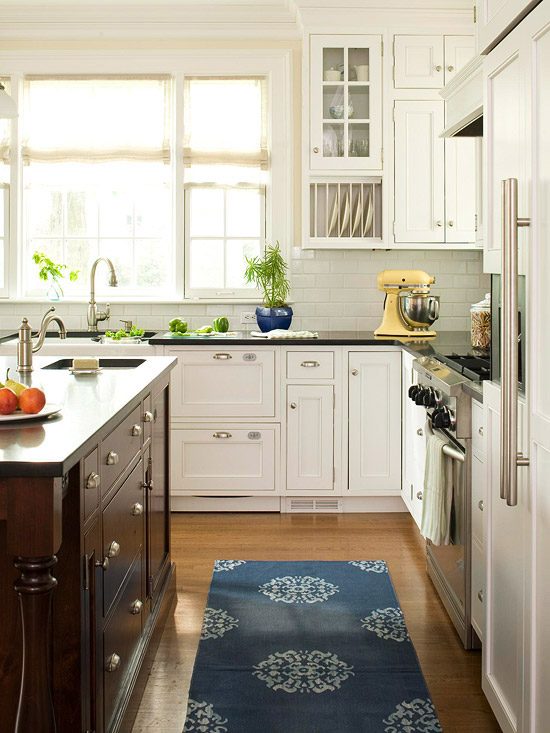 White Kitchen with Black Counters and Blue Patterned Rug